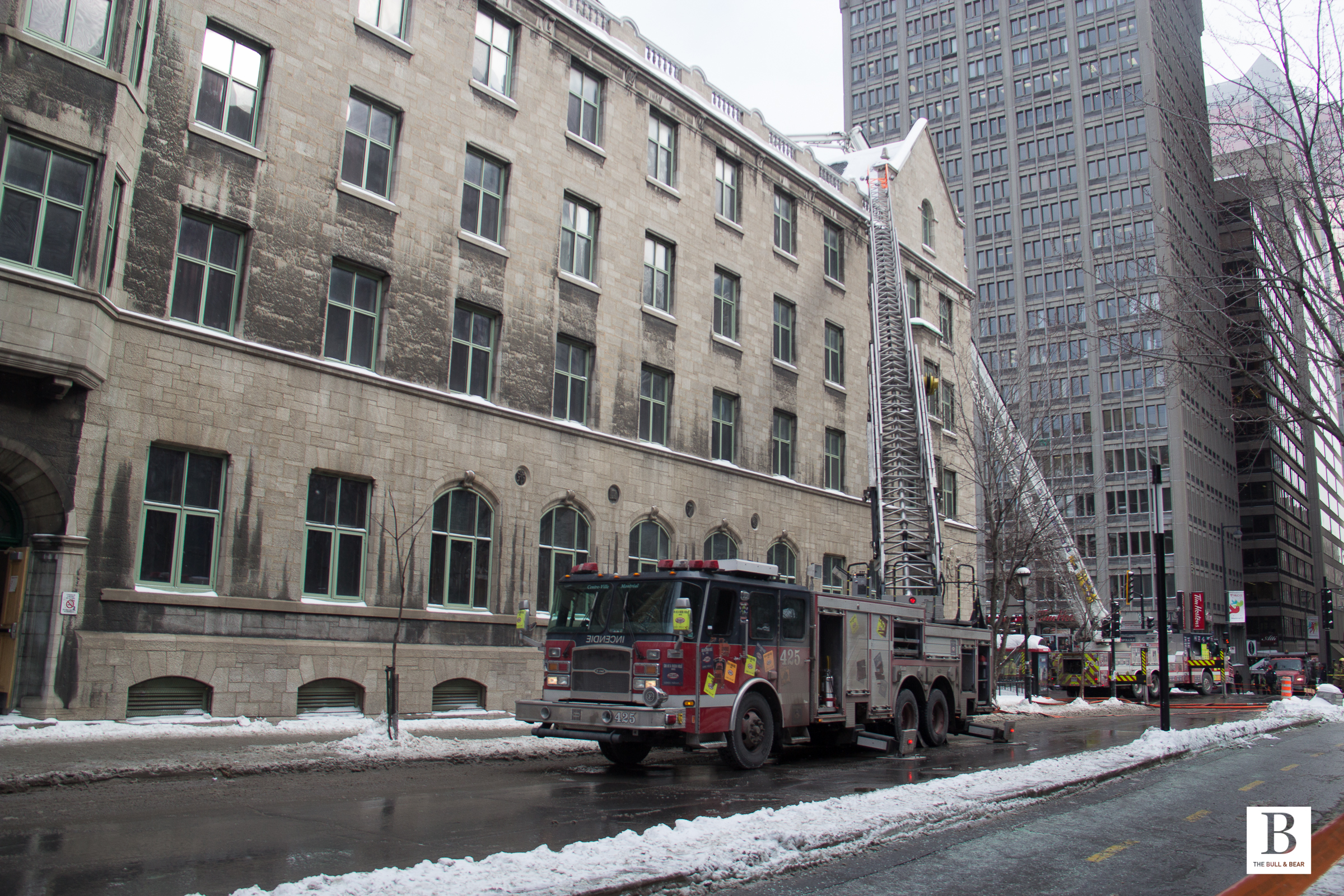 A firetruck extends a ladder to firefighters on the roof of RVC.